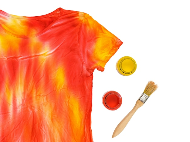 Two tubes of paint, brush and t-shirt in tie dye style isolated. staining fabric in tie dye style.