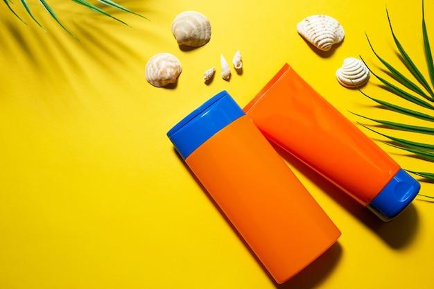 Две трубки с мокапами солнцезащитных кремов на желтом летнем фоне. защита кожи от ультрафиолета с помощью spf-фильтра, шампуня для ухода за волосами и кондиционера. безопасный загар на пляже. планировка квартиры - курорт на море.