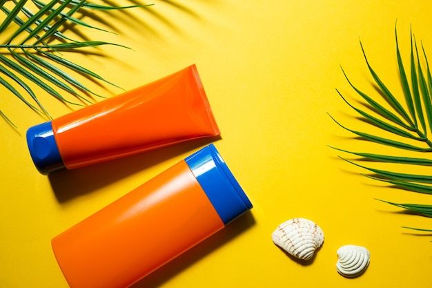 Two tubes with mock up sunscreens on a yellow summer background. uv protection of the skin with an spf filter, hair care-shampoo and conditioner. a safe tan on the beach. flat lay - resort on the sea.