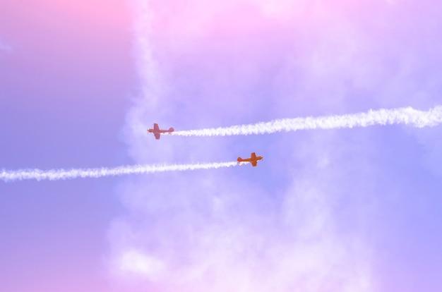 Два турбовинтовых самолета со следом белого дыма на фоне голубого неба.