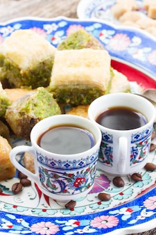Two turkish cups of black coffee with sweets