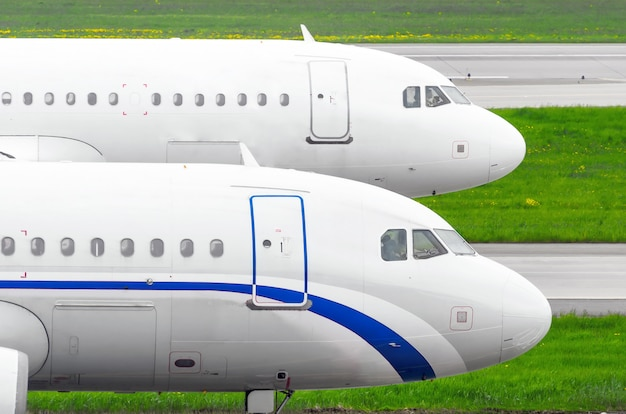 Two twin airplanes on the runway at the airport