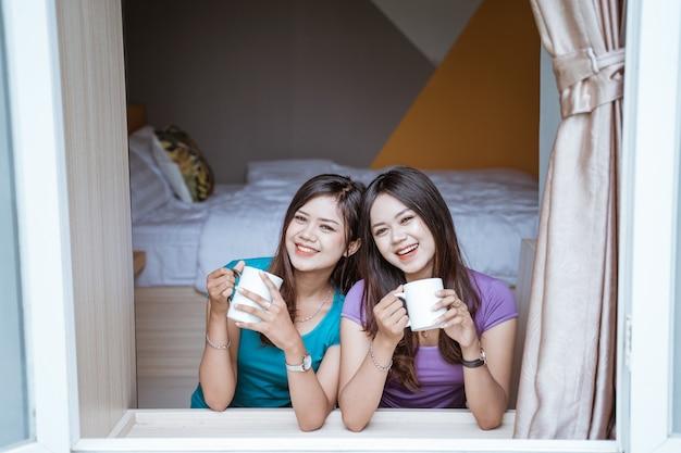 그녀의 집에있는 창 근처에 뜨거운 차 또는 커피 한 잔을 들고 두 쌍둥이 매력적인 아시아 자매