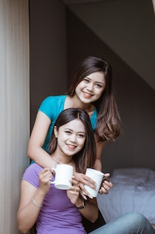 Two twin attractive asian sister holding a cup with hot tea or coffee near the window in her home