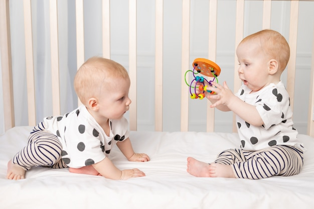Two twin babies 8 months old playing in the crib, early development of children up to a year, the concept of the relationship of children of brother and sister, a place for text