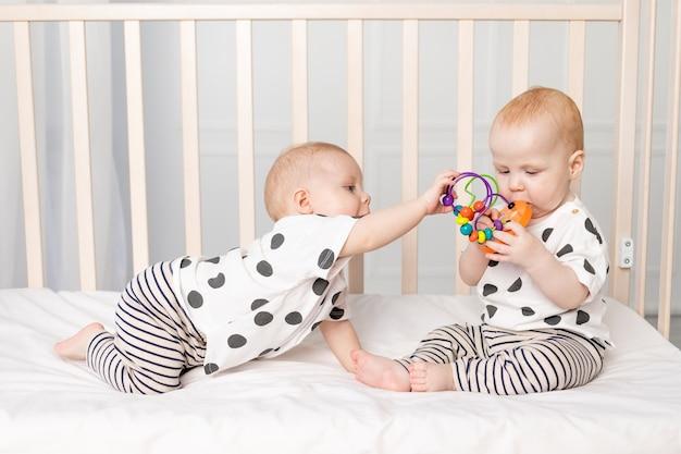 2人の双子の赤ちゃんがベビーベッドで遊ぶ