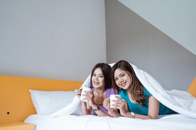 함께 침대에 누워있는 동안 뜨거운 차 또는 커피 한 잔을 들고 두 쌍둥이 아름다운 아시아 여자