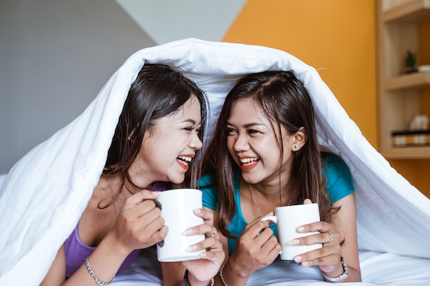 Two twin beautiful asian woman holding a cup with hot tea or coffee while laying on the bed together