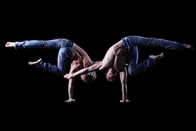 벌거 벗은 몸통을 가진 청바지를 입은 두 명의 쌍둥이 형제는 검은 배경에서 곡예 요소를 수행합니다. 프리미엄 사진