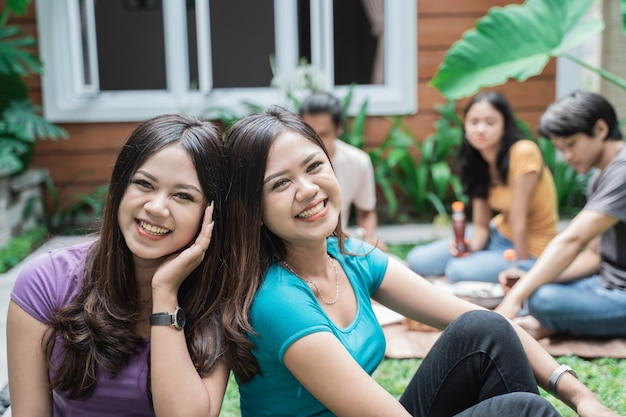 Two twin sister enjoy picnic together with friends in the backyard