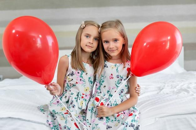 아름다운 드레스를 입은 두 쌍둥이 자매가 풍선을 손에 들고 호텔의 침대에 앉아 있습니다.
