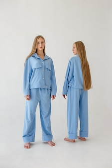 Two twin sisters with long hair posing in oversize clothes on white background