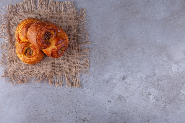 Two twirl fragrant pastries placed on stone background.