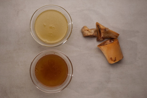 Two types of bone broth in transparent cups on stone table, top view, close-up. fish and meat broth contain healthy collagen.