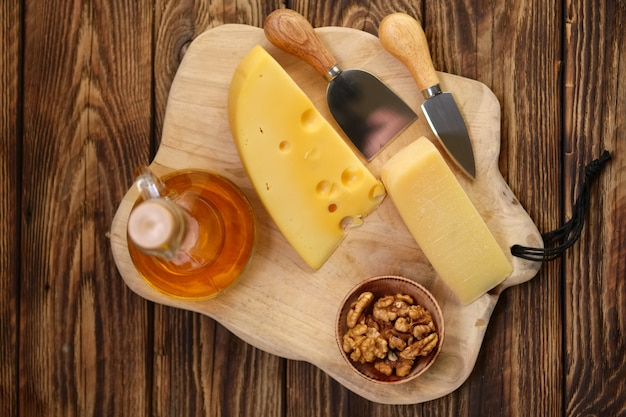 Two types of cheeses - parmesan and gouda with walnuts and honey on wooden board with cheese knives