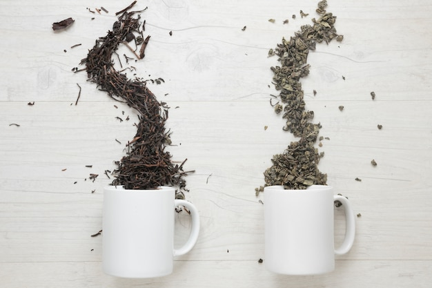 Two types of dry tea leaves falling from cup over white wooden table
