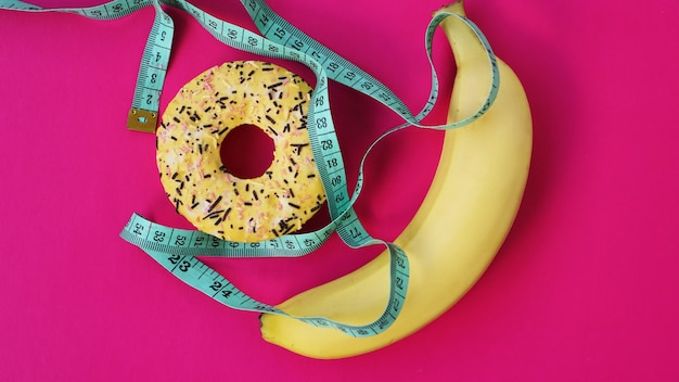 Two types of food, healthy and unhealthy, banana and donut, diet and obesity, health concept on a pink background