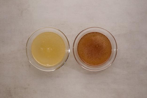 石のテーブルの透明なカップに入った2種類の骨スープ。魚や肉のスープには健康的なコラーゲンが含まれています。