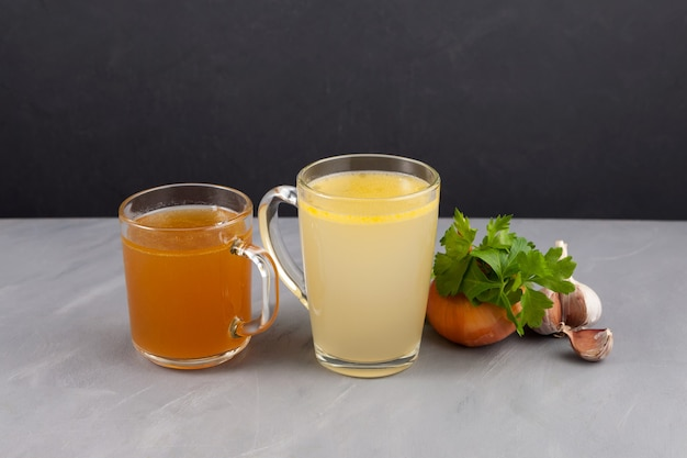 透明なカップに入った2種類の骨スープ(黄色と茶色)。魚や肉のスープには健康的なコラーゲンが含まれています。