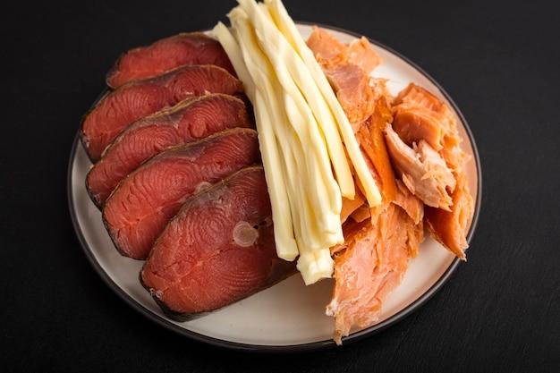 Два вида рыбы холодного и горячего копчения и сыр чечил. крупный план. закуска к пиву