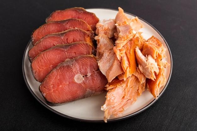 На тарелке два вида рыбы холодного и горячего копчения. крупный план
