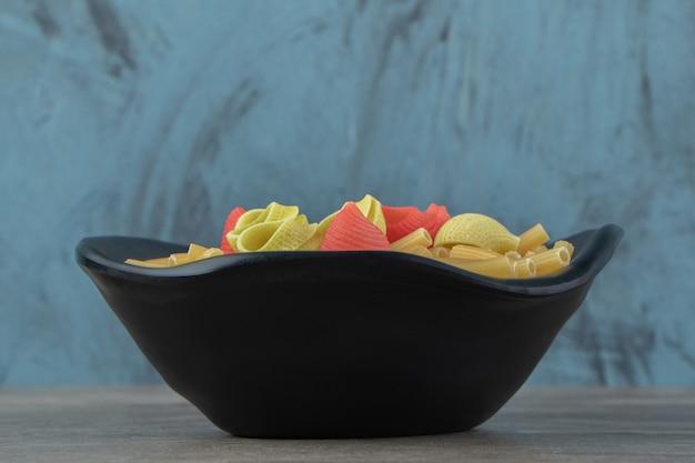 Два вида сырых макарон в черной миске.