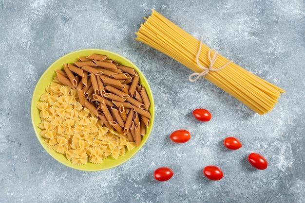 Два вида сырых макарон на тарелке с помидорами и спагетти.