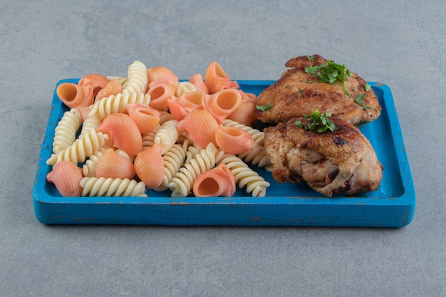 Two types of pasta and grilled chicken on blue plate.