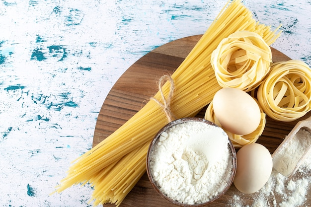 Two types raw pasta with eggs and bowl of flour on wooden board.