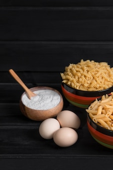 Two types of raw pasta with flour and chicken eggs placed on wooden table. high quality photo