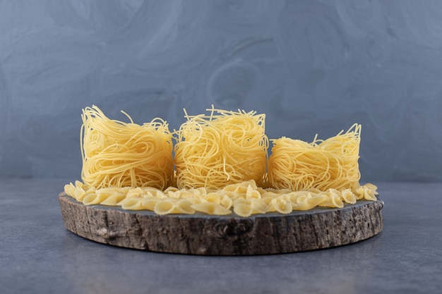Two types of raw pasta on wood piece.
