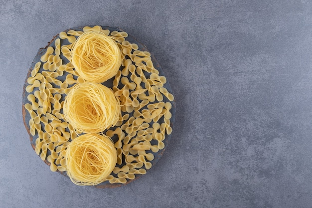 Due tipi di pasta cruda sul pezzo di legno.