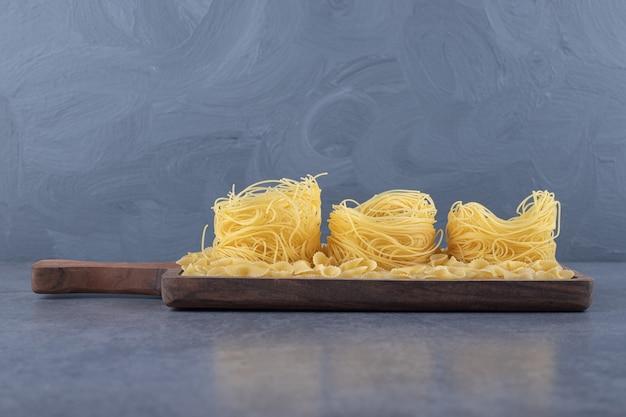 Due tipi di pasta cruda su tavola di legno.
