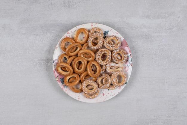 Due tipi di gustosi anelli pretzel sul piatto bianco.
