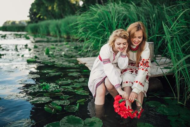 Две равные девушки, возлагающие цветок венок в воду