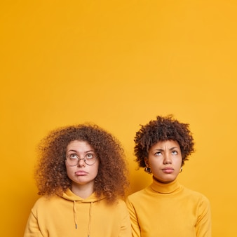 Two unhappy curly haired women of different nationalities focused above on something upleasant stand shoulder to shoulder isolated over yellow wall with copy space for your advertising content.