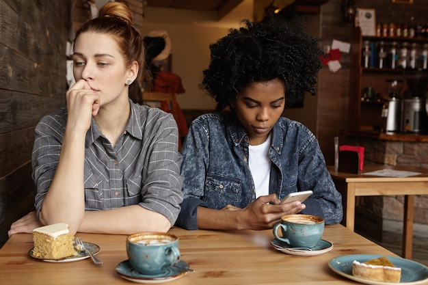 Two unhappy lesbians not talking to each other after having quarrel during lunch at coffee shop