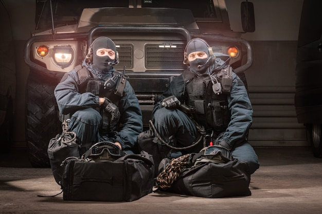 Two uniformed commandos sit in a hangar with a military truck