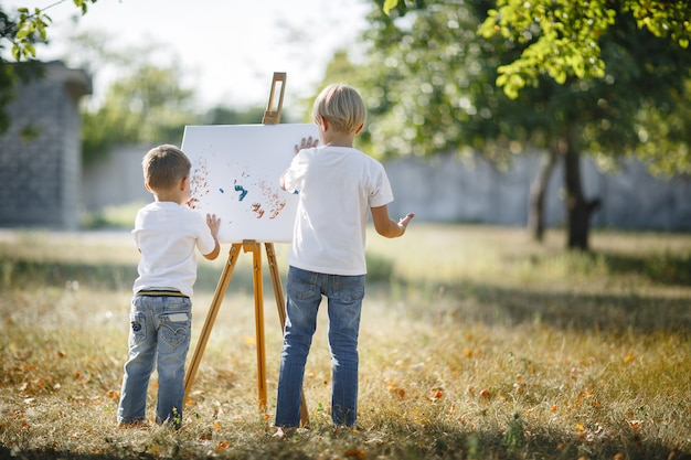 Two unrecognizable children drawing outdoors