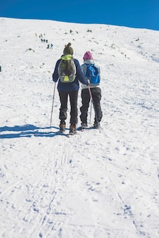 Two unrecognizable people walking through snow on the mountain