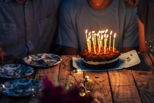 誕生日や記念日のお祝いのためにおいしいチョコレートケーキにろうそくを燃やしている2人の認識できない人々。燃えるろうそくとチョコレートのバースデーケーキ