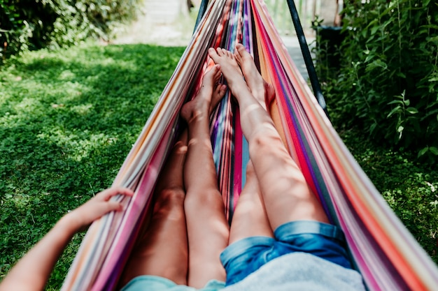 Two unrecognizable teenager girls lying on colorful hammock at the garden