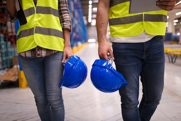 Two unrecognizable workers in reflective suit walking through warehouse and holding blue protective hardhats
