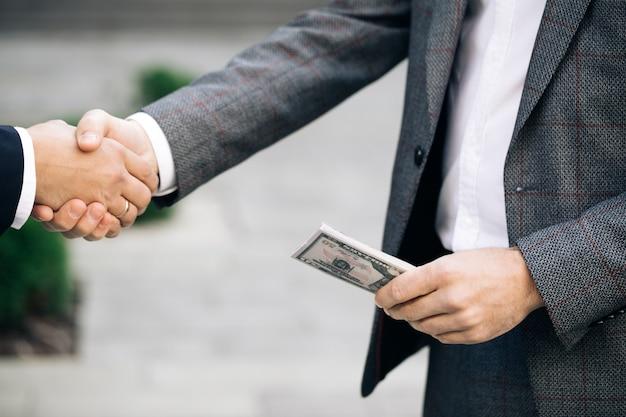 握手する2人の認識されていないビジネスパートナーの同僚がちょうど良い取引をしました