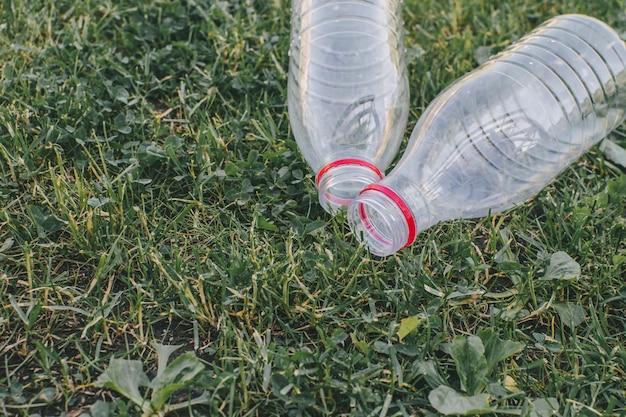 Две использованные пластиковые бутылки на фоне травы. концепция разделения отходов.
