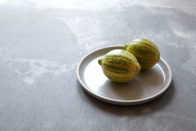 灰色のプレートに緑の縞模様の皮が付いた2つの多彩なピンクレモン