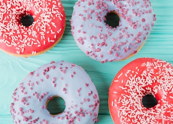 Two various types of delicious donuts on wooden table