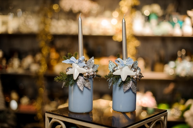 Two vase with christmas decor composition of fir-tree branches, toy stars, silver leaves and ornaments, and candles