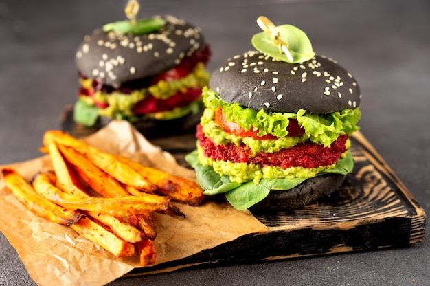 Two vegan black burgers with fried sweet potato