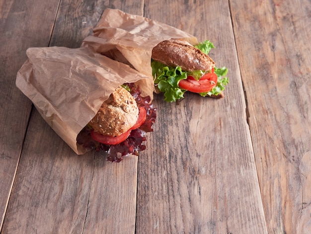 Two vegetable sandwich baguettes on paper bags, isolated on a wooden background
